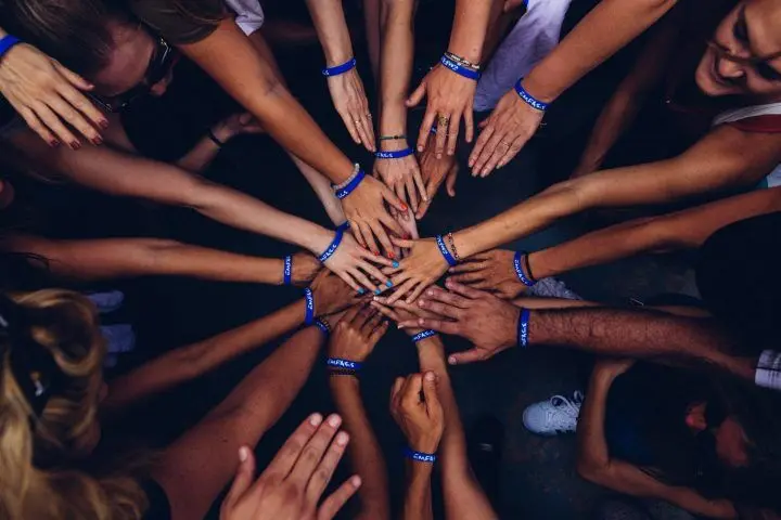 An image showing the hands of lotto syndicate members on top of one another vying for success in lotto. This is the concept of lottery syndicate. All members put their money together to increase their chances of winning through covering principle.